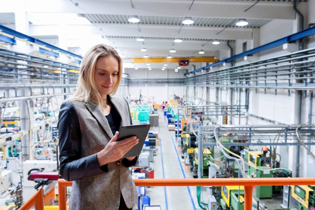 woman looking at electronic tablet in production factory